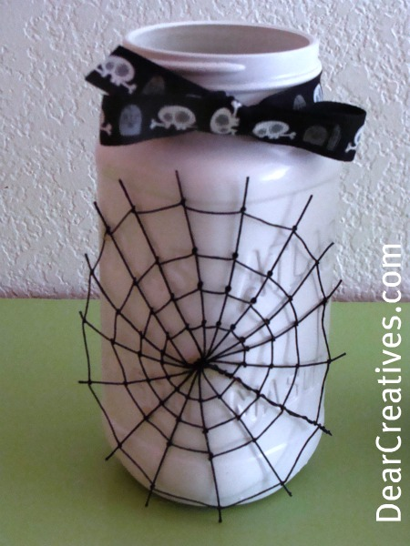 mason jar decorated for Halloween with a spider web and skull ribbon - DIY and Halloween Ideas at DearCreatives.com