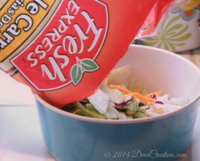 Fresh Express salad being poured into a bowl_