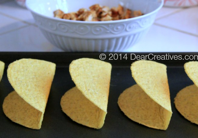 Taco shells on a baking pan_ bowl of chopped chicken_