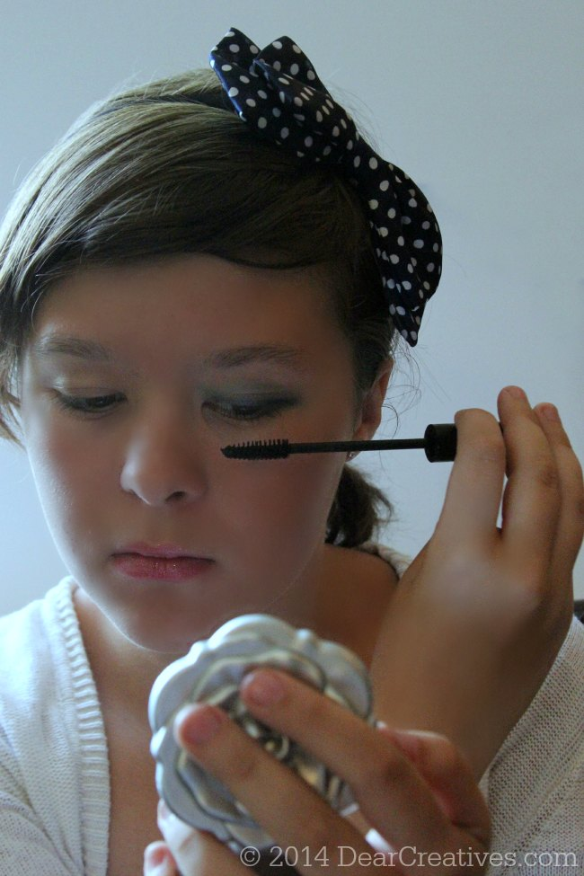 Teen girl putting on mascara