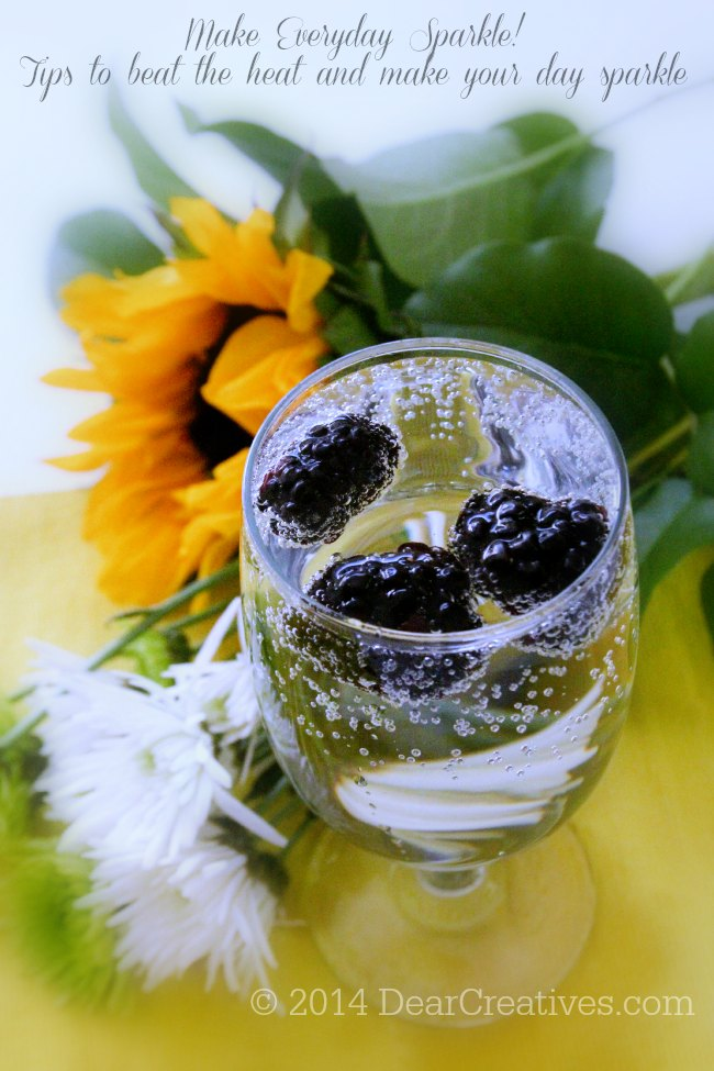 sparkling water in a glass with blackberries and flowers next to it