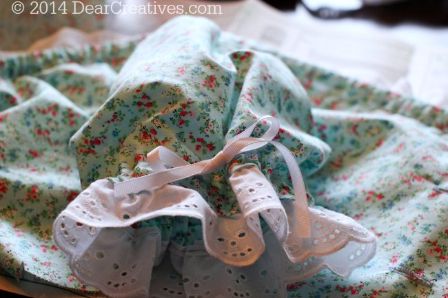 Sleeve of costume with eyelet lace and ribbon tie_