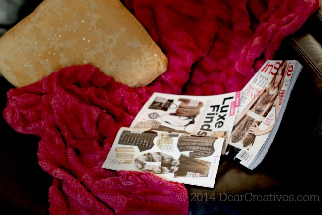 Throw pillow, blanket and fashion magazines on a couch_