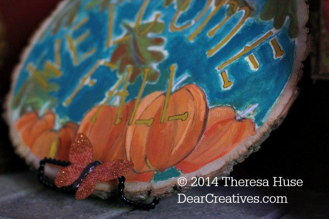 Close up of fall painting on wood round of pumkins with welcome fall stencil lettering_