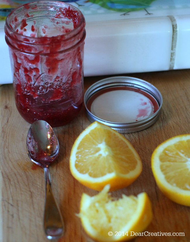 Homemade Cranberry Sauce Raspberry Jam in a jar and orange slices_