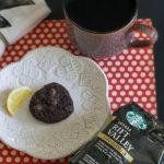 Coffee Lovers Coffee and a bag of Starbucks Coffee next to a plate with a lemon and chocolate cookie