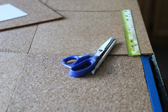 Measuring and fitting cork tiles into the bulletin board frame.