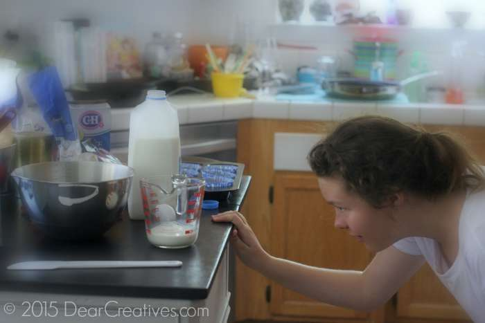 Teen checking measuring cup measurement for baking