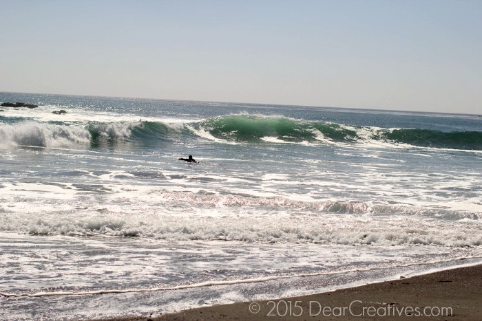 surfer swimming out to waves