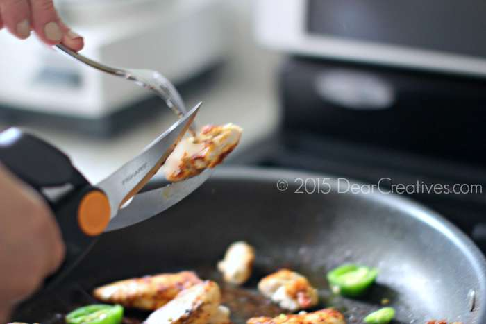 Cutting cooked chicken with heavy duty butcher shears