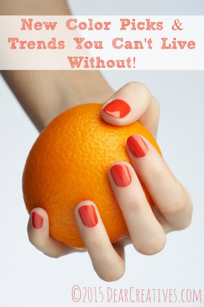 Closeup image of woman hand with beautiful orange manicure holding orange