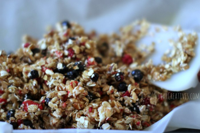 Granola on parchment paper being pressed down