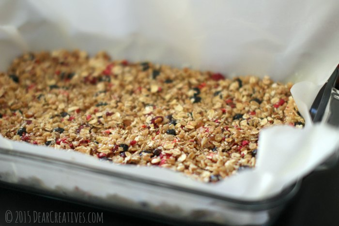 Granola pressed down in a baking dish ready to bake for granola bars