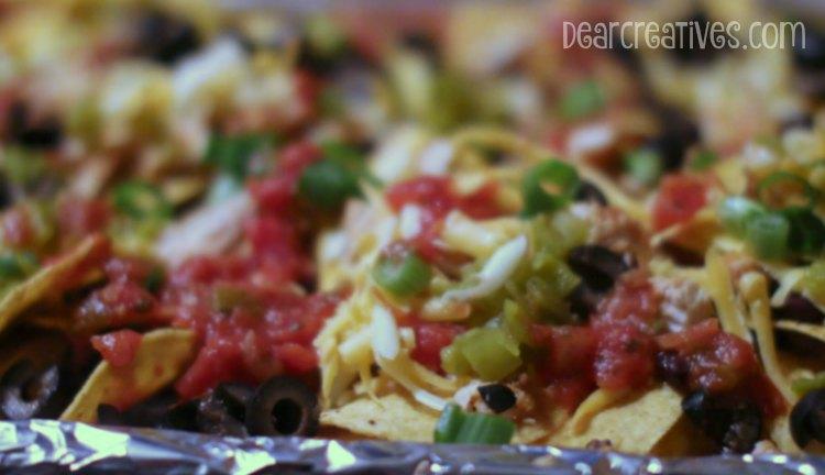 Easy Recipe loading up nachos onto a baking sheet