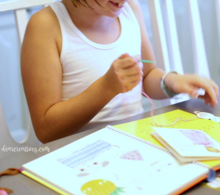 kids-crafts-girl-learning-to-stitch-with-stitching-cards-from-a-kids-book