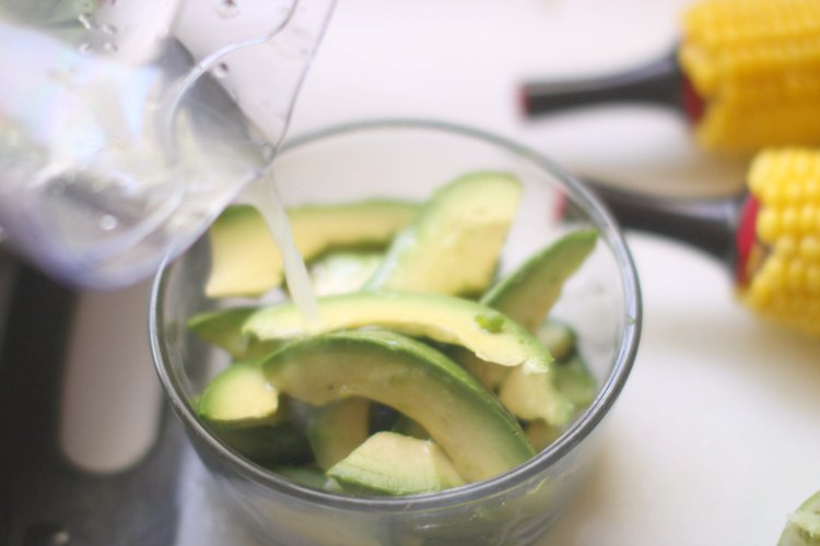 Pouring lime juice onto avocados for the Southwest Salad Recipe- DearCreatives.com