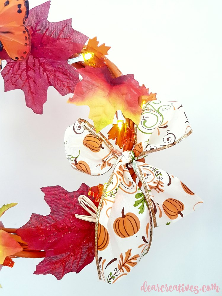Close up of bow on grapevine wreath made for fall. See diy at DearCreatives.com