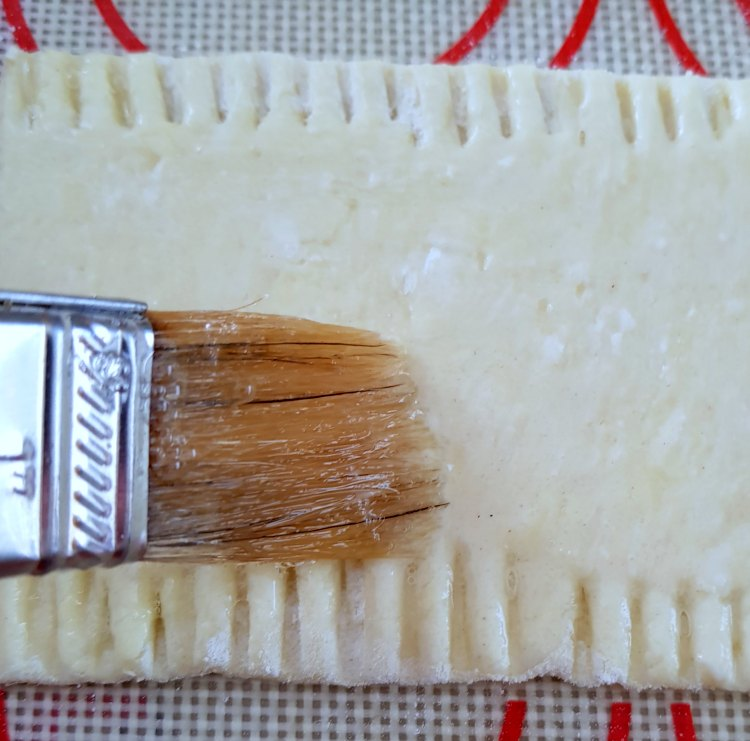 Putting egg wash on the puff pastry for an appetizer recipe. DearCreatives.com