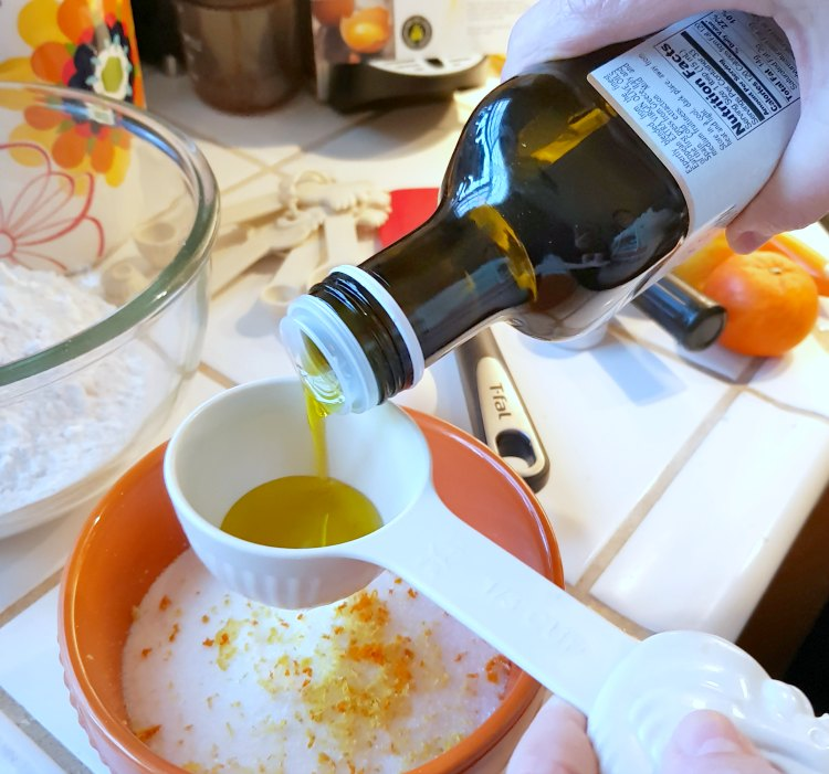 pouring extra virgin olive oil into a measuring cup for a sugar cookies recipe DearCreatives.com