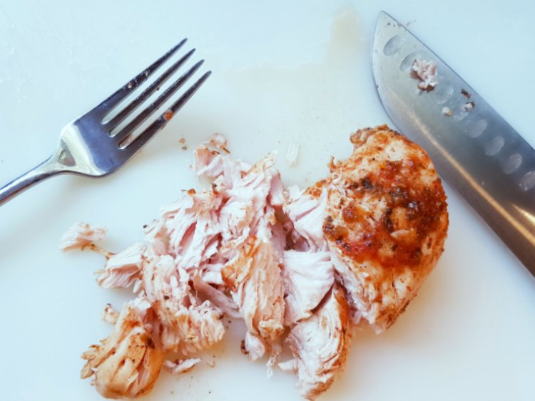 Chicken being cut and shredded for chicken tacos on a cutting board with a knife and fork. DearCreatives.com