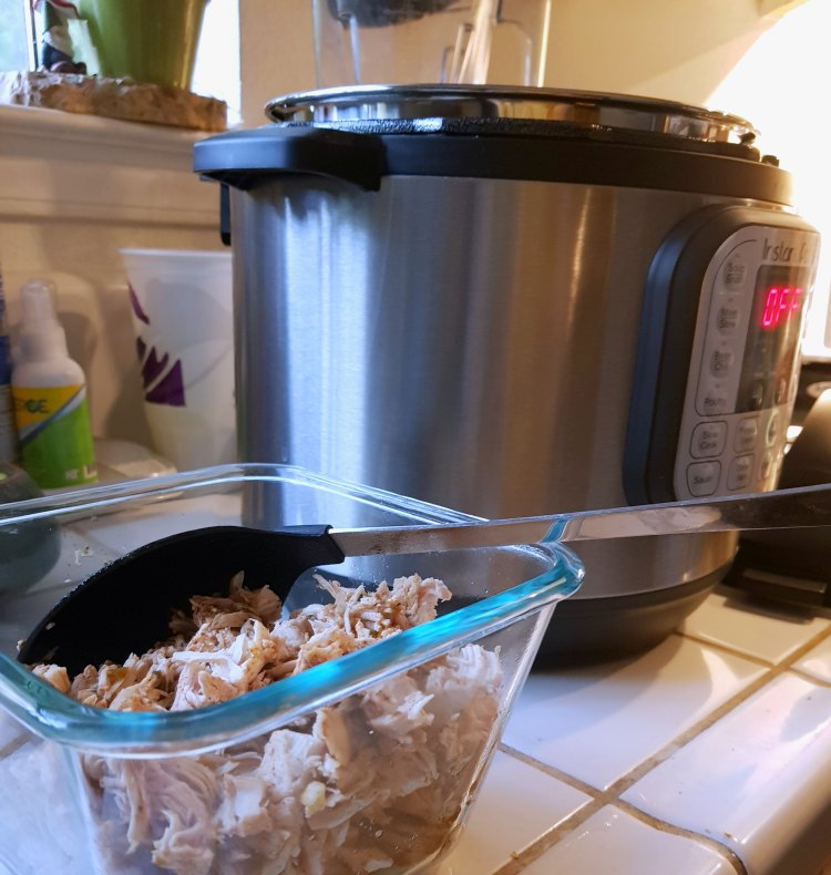 Shredded cut up chicken in a glass storage container next to an instant pot on the kitchen counter. DearCreatives.com