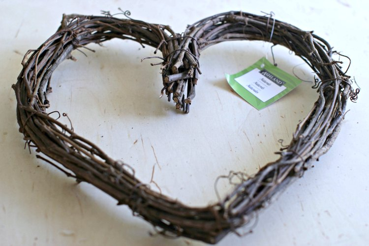 grapevine wreath laying on a wood surface ready to be decorated. Make this easy fall wreath with the directions at DearCreatives.com