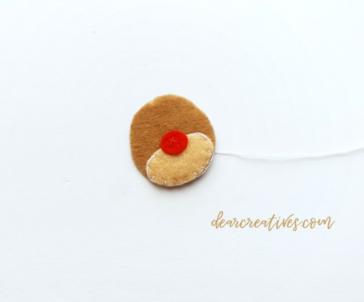 Sewing on the nose for Rudolph the red nosed reindeer. Felt Christmas ornament Step 2 of the diy DearCreatives.com