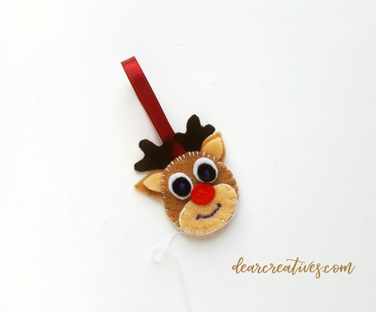 felt reindeer head with ribbon attached to hang ornament on holiday tree Full tutorial at DearCreatives.com