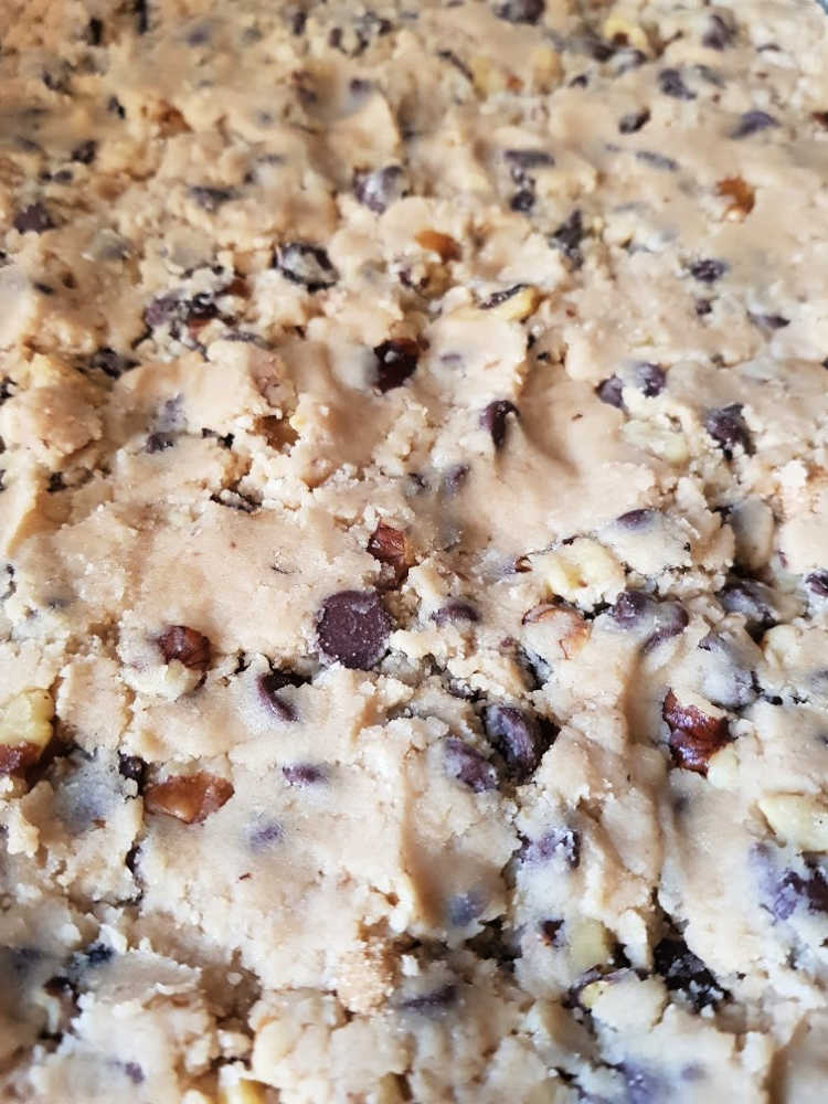 Cookie dough pressed onto a sheet pan for baking chocolate chip cookie bars DearCreatives.com