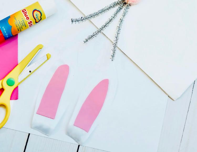 Cutting bunny ears to glue onto the bunny bag. How to make a bunny bag at DearCreatives.com #nosew #bunnybag #bunnypaperbag #dearcreatives