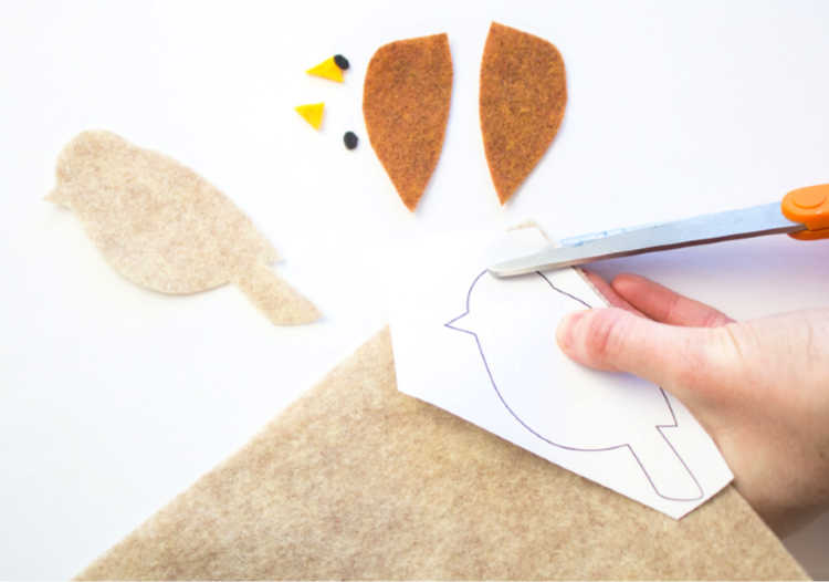 Cutting out the bird parts from the free printable bird template - Template and instructions at DearCreatives.com