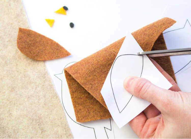 Cutting the wings for the felt bird to make a bookmark. Find this felt craft and more at DearCreatives.com