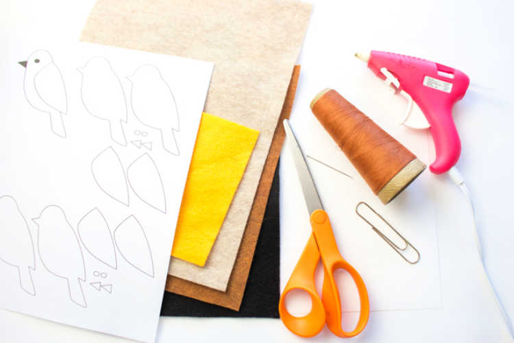 Felt supplies, craft supplies, a giant paper clip, scissors, thread, printed bird template and other supplies for making a felt bookmark. DIY Felt Bird Bookmark at DearCreatives.com