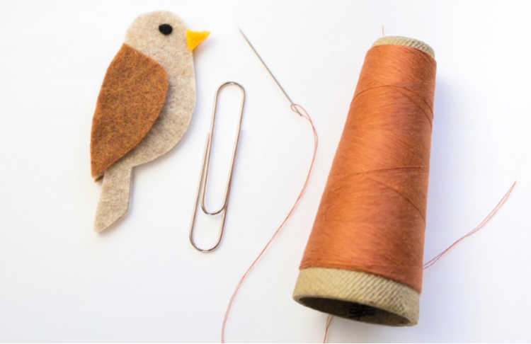 Get ready to sew the paper clip securing under the wing. Full directions for this felt bird bookmark at DearCreatives.com