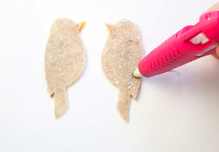 Hot gluing the inside of the felt cut out bird to glue the two sides together. Full instructions for how to make the felt bookmarks at DearCreatives.com