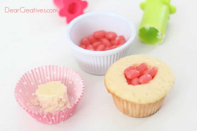 Adding jelly beans into the hole of the cupcake that was cored out. Recipe and how to at DearCreatives.com