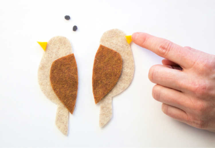 gluing beaks onto the felt birds - see all the steps of this felt craft at DearCreatives.com