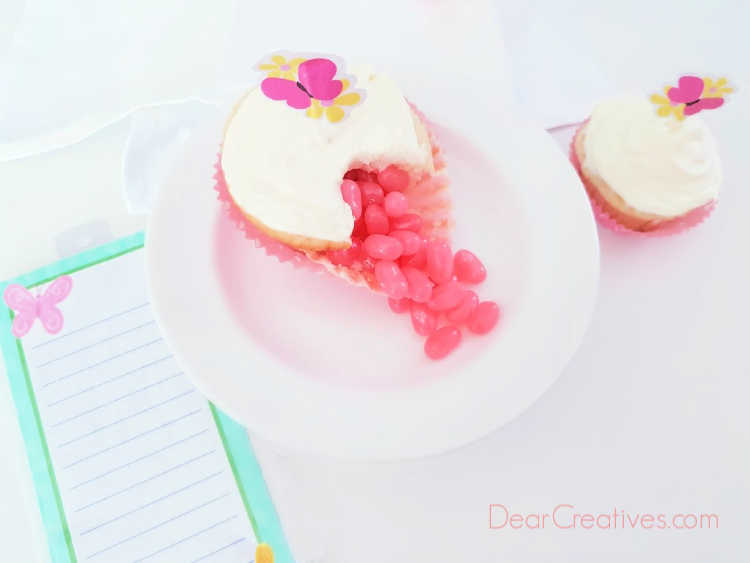jelly bean cupcake - jelly beans spilling out of a cupcake sitting on a plate. Cupcake with a butterfly topper. Recipe and tutorial at DearCreatives.com #jellybeancupcakes #howto
