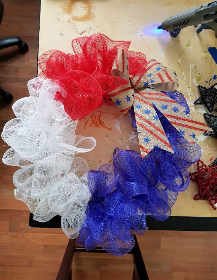Adding a bow to the mesh wreath. how-to instructions at DearCreatives.com