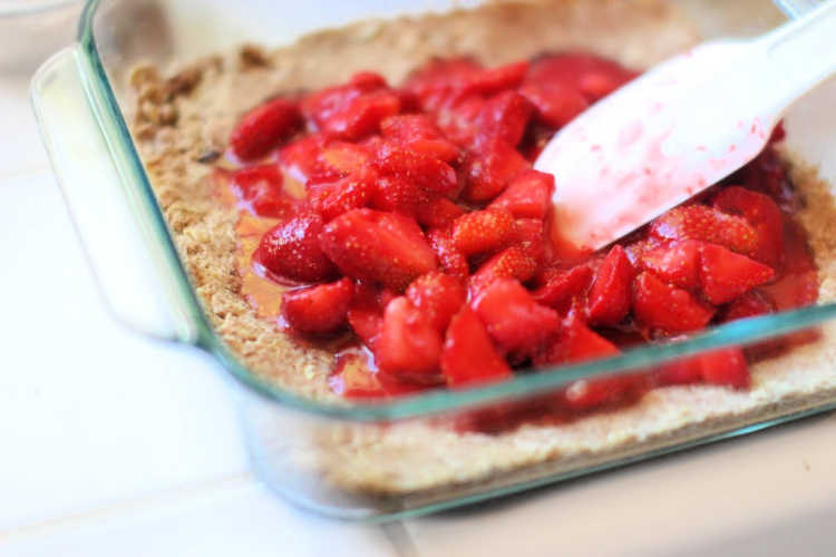Spreading a macerated strawberries to the top of the strawberry bars crust. DearCreatives.com