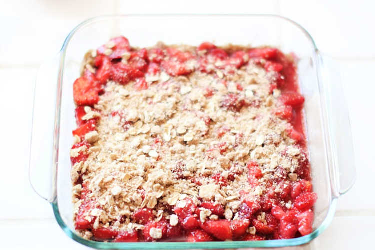 Spreading crumb topping on the strawberries for a dessert strawberry recipe. DearCreatives.com