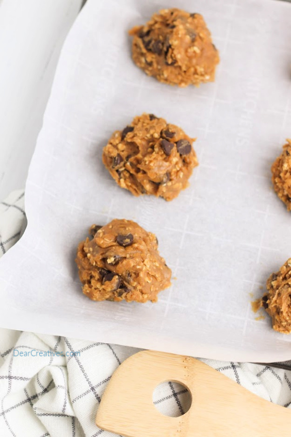 cookie dough on parchment paper on a baking sheet. Pumpkin oatmeal cookies recipe at DearCreatives.com