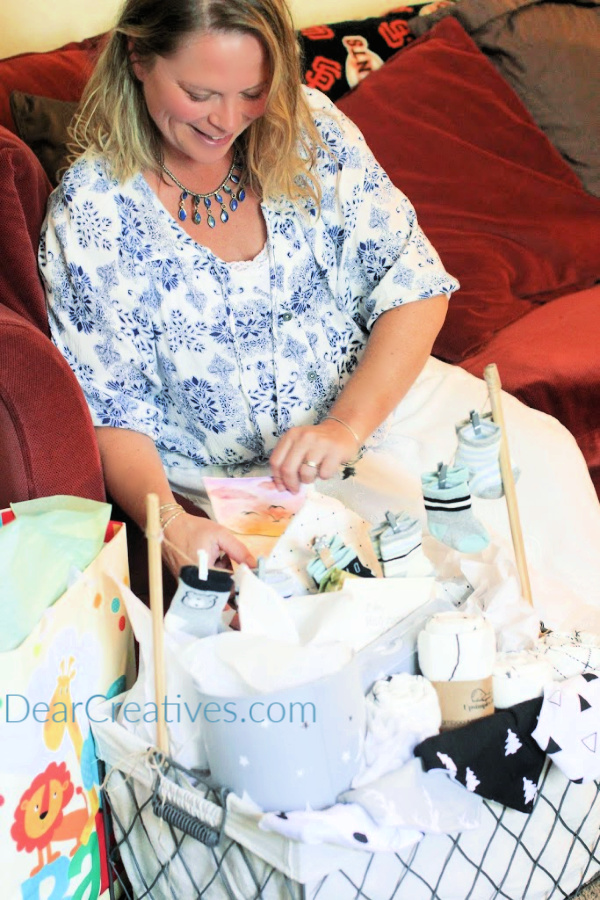 pregnant mom = Mom to be opening gifts at a baby shower - DearCreatives.com