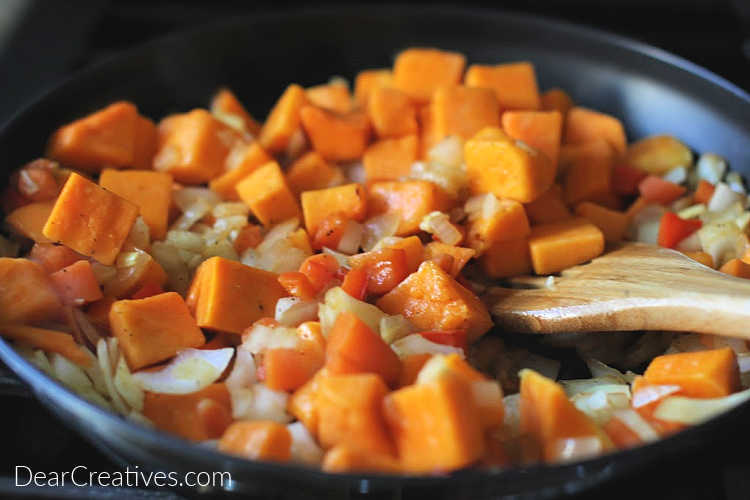 Adding butternut squash to the onions, garlic, carrots and red bell peppers for chili with black beans and squash. DearCreatives.com