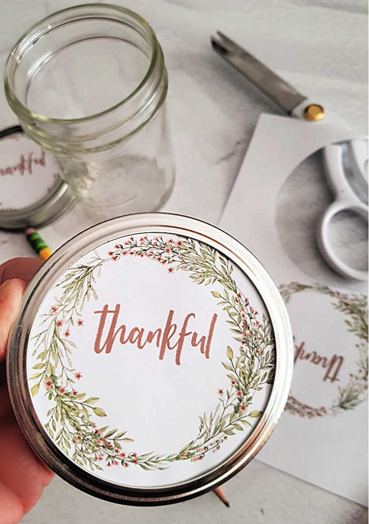 Inserting the printable label on the inside of the lid with pretty fall design facing to the top_front. Free printable and autumn fall Thanksgiving mason jar craft at DearCreatives.com