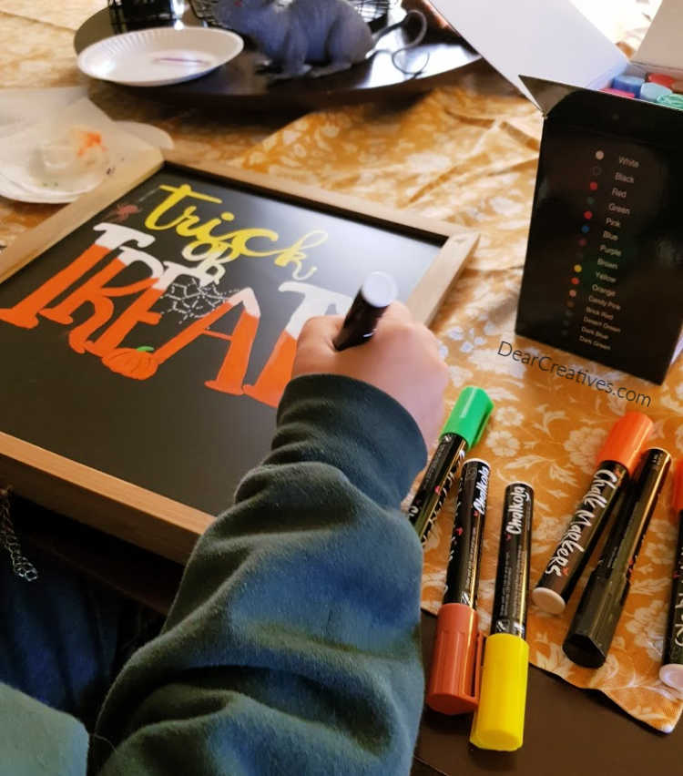 Making a chalkboard sign that says Trick or Treat. Hand lettering and chalkboard art tips at DearCreatives.com