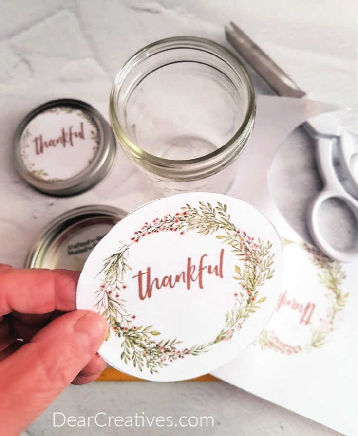 holding the cut out printable thankful that is ready to add to the jar lid - Grab this fall DIY_craft plus, free printables at DearCreatives.com