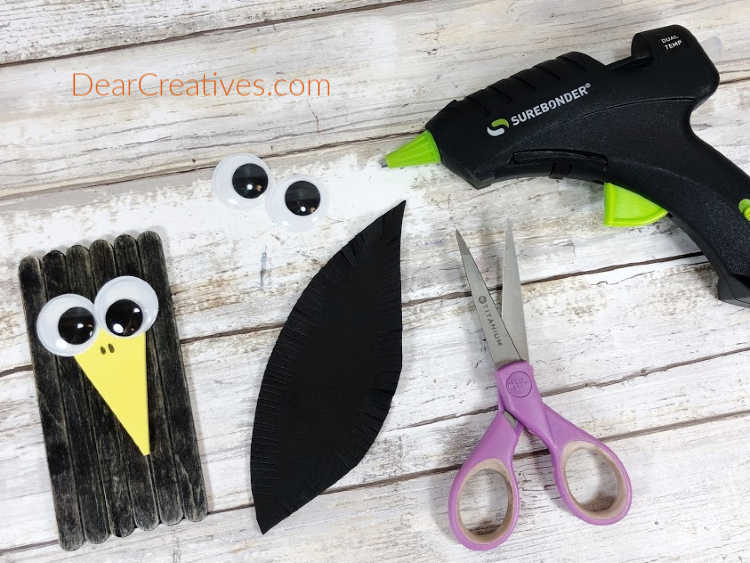 Step 5 - Embellish the Crow with two wiggle eyes, a large yellow craft foam triangle beak...See full instructions for making a crow, scarecrow and corn from craft sticks - DearCreatives.com