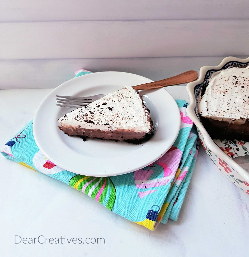 Slice of a chocolate cream pie on a plate with a fork with the no bake chocolate pie next to it. Recipe DearCreatives.com