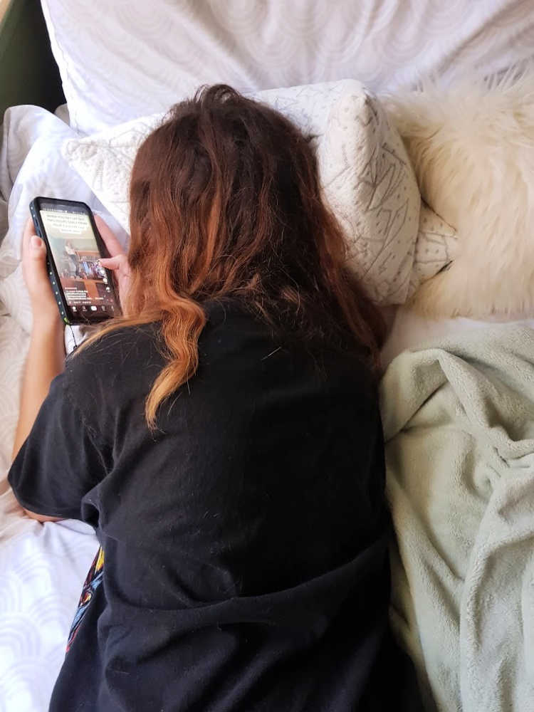 Resting on a buckwheat pillow while on a cell phone. DearCreatives.com